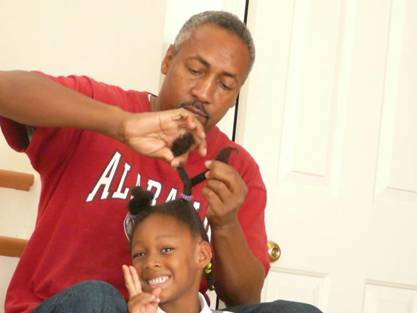 Father brading his daugher hair